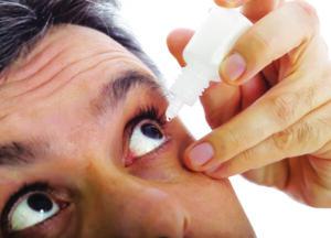 man taking eye drop medicine